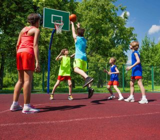 Team in colorful uniforms playing basketball game on the ground during sunny summer day together