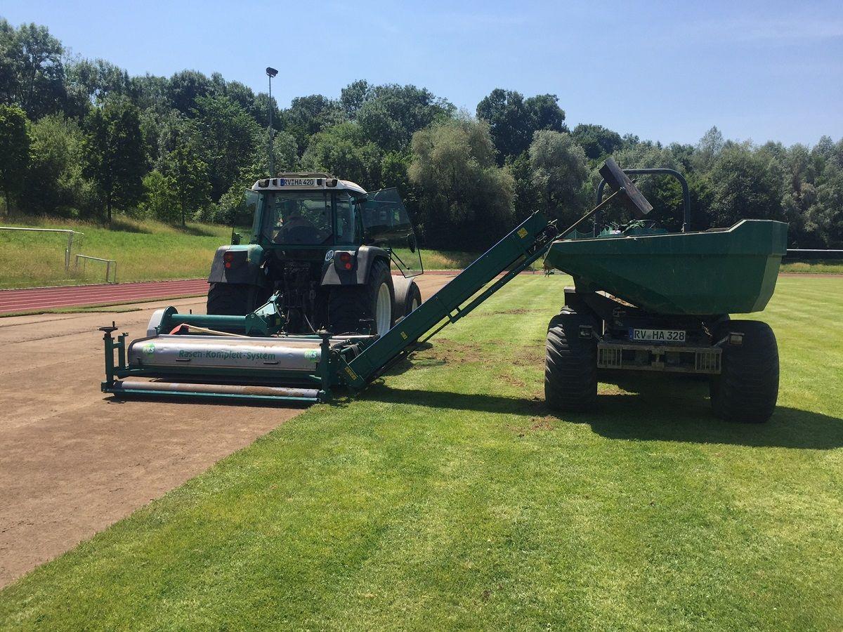 Maschinen pflegen Rasen eines Sportplatzes