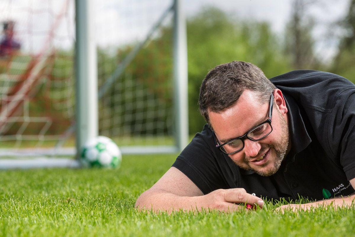 Mann liegt auf Rasenfläche vor Tor und betrachtet das Gras